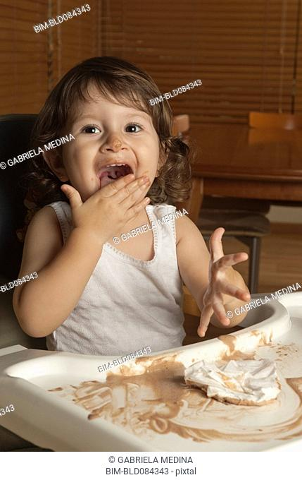 Hispanic baby in high chair licking hand