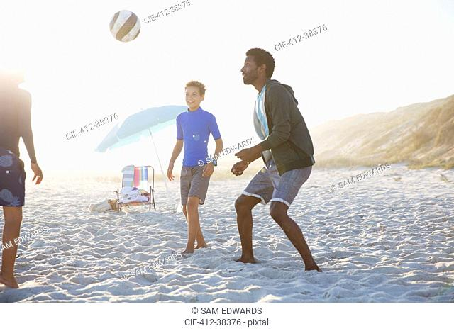 Father and children playing soccer on sunny summer beach