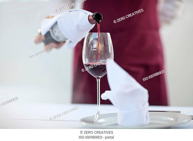 Waiter in restaurant pouring glass of red wine, mid section