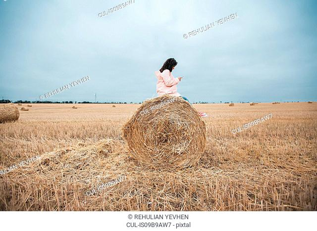 Woman in raincoat on hay bale, Odessa, Ukraine