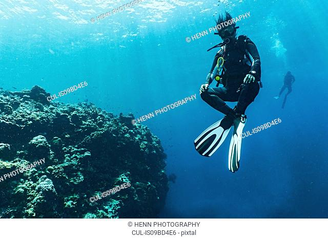 Underwater view of diver hovering at 5 m safety stop over coral reef at the Tubbataha Reefs Natural Park, Cagayancillo, Palawan, Philippines