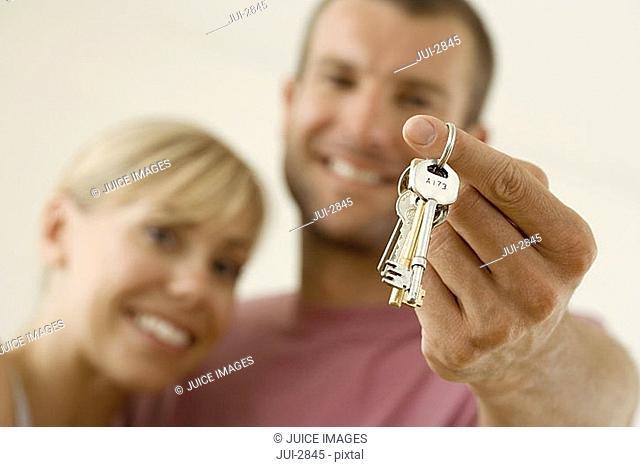 Couple smiling, portrait, man holding set of keys, close-up, focus on foreground