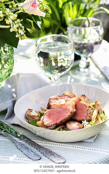A lamb dish on a summery table in the open air