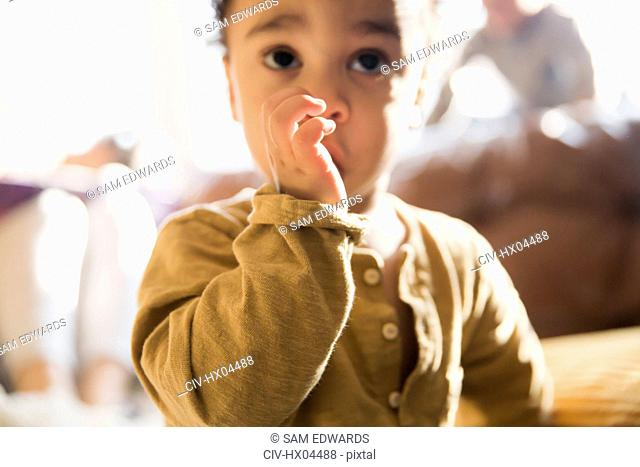 Close up innocent baby boy sucking thumb