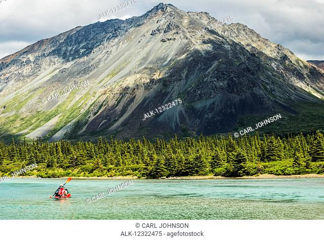 A kayaker paddles across one of the Twin Lakes in Lake Clark National Park & Preserve, Southcentral Alaska, USA