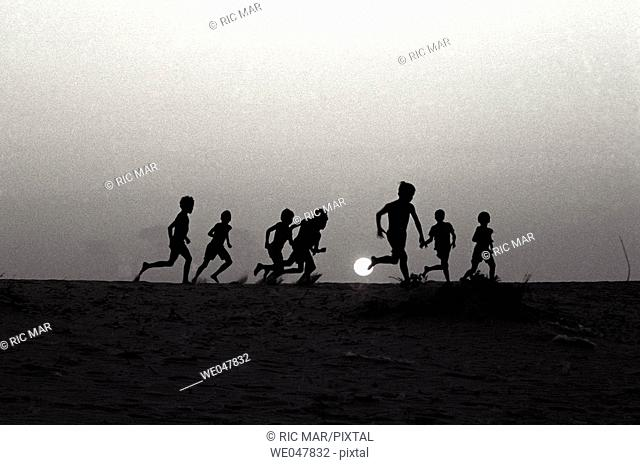 Around 12 years old boys playing soccer in the beach. Brazil