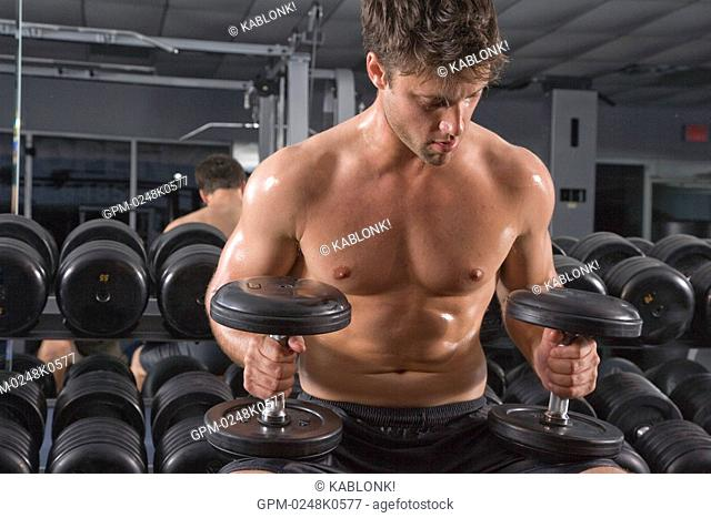 Young man holding dumbbells in gym with mirror in background