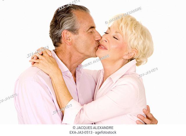 Studio shot of senior couple hugging and kissing