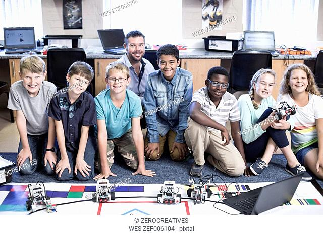 Portrait of smiling kids with teacher in robotics class
