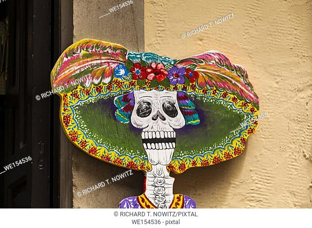 A store sign using a painting of a skull with a hat, a Day of the Dead motif used in Guanajuato, Mexico