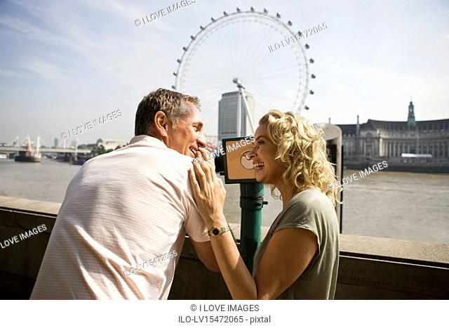 A middle-aged couple using a telescope in front of the London Eye