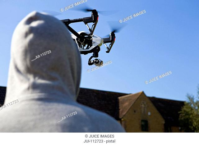 Hooded man looking up at surveillance drone in blue sky
