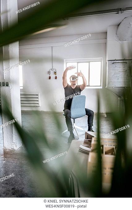Man sitting on chair in empty loft wearing VR glasses