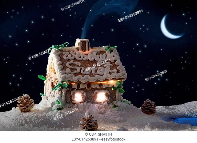 Snowy gingerbread cottage at night in winter