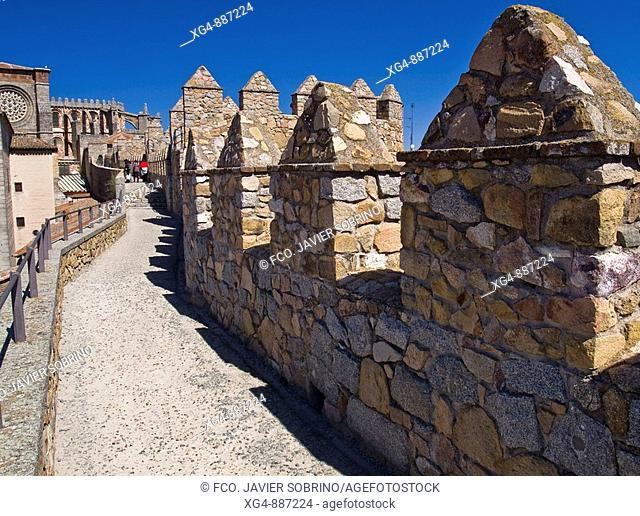 Sentry walk and merlons, East section of medieval city walls (12th century) and cathedral in background, Avila. Castilla-Leon, Spain