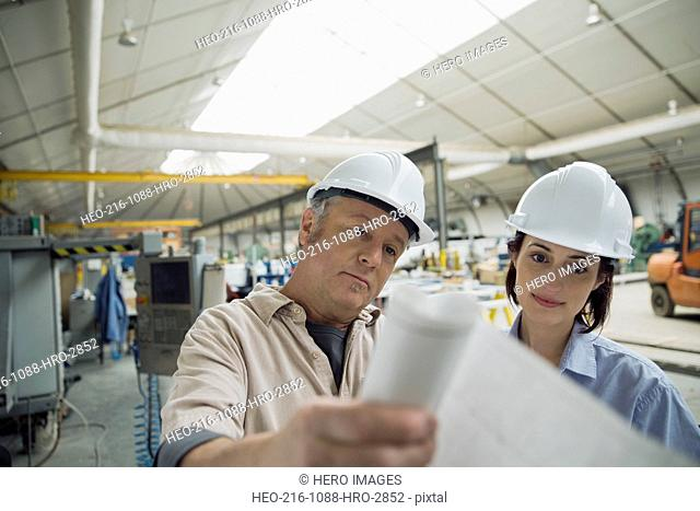 Workers reviewing blueprints in manufacturing plant