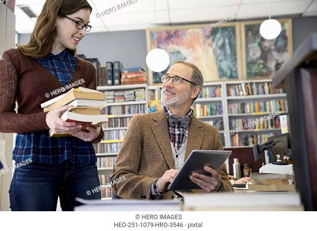 Bookstore owner with digital tablet talking to woman