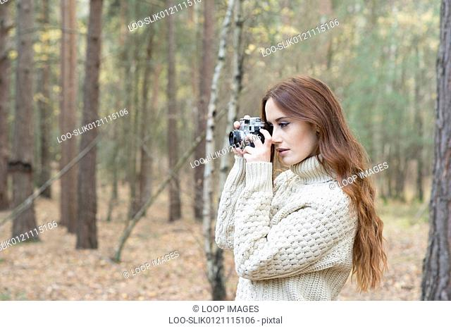 A young woman using a vintage camera in a forest in Autumn