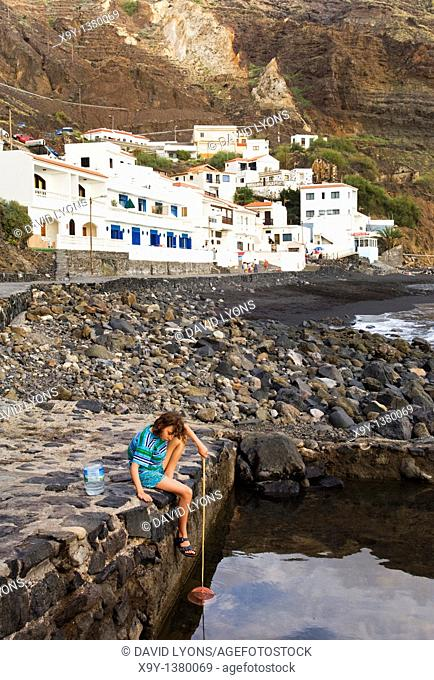Alojera Hotel and apartments on Playa de Alojera black sand beach, west coast of La Gomera, Canary Islands  Girl crab fishing