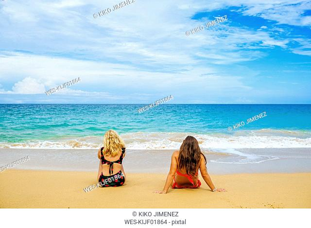 Panama, Bocas del Toro, Playa Bluff, Two women in bikinis sitting on the beach