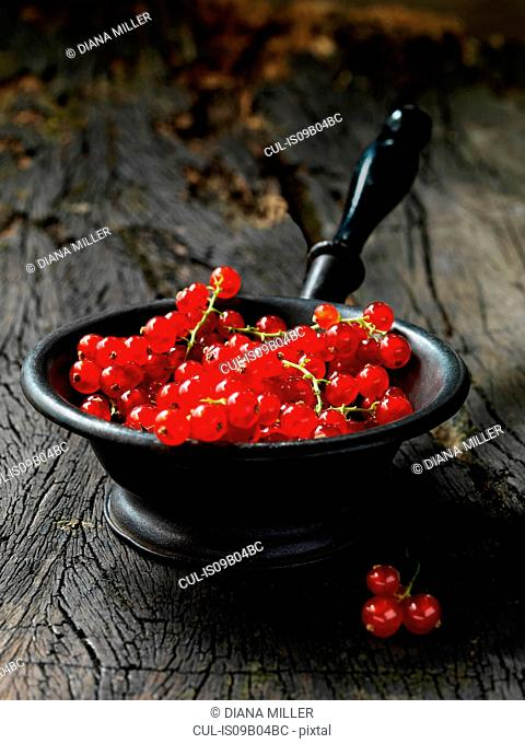 Red currants in small vintage metal sieve, rustic wooden table