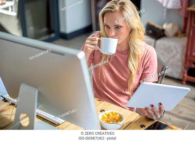Woman at computer drinking coffee holding digital tablet