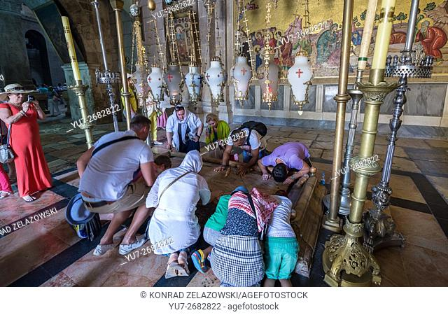 Pilgrims praying next to Stone of Anointing in Church of Holy Sepulchre, Jerusalem and mosaic depicts anointing of Jesus body