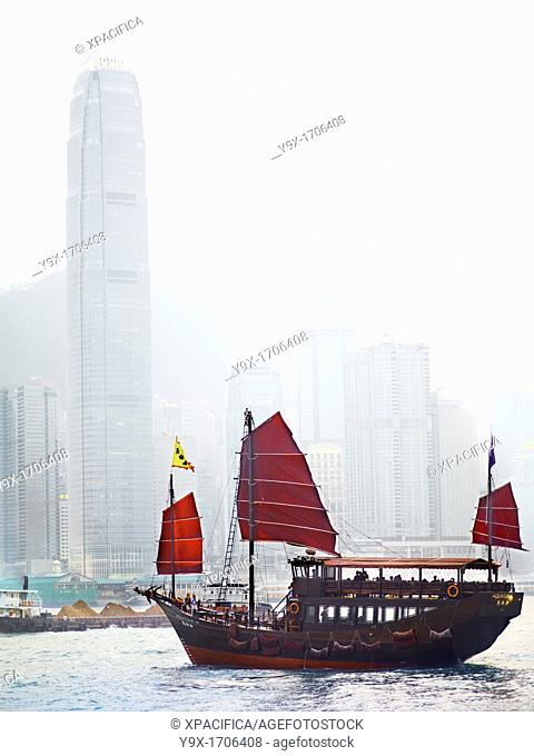 An old style Hong Kong Junk boat sails in Victoria Harbour in Hong Kong