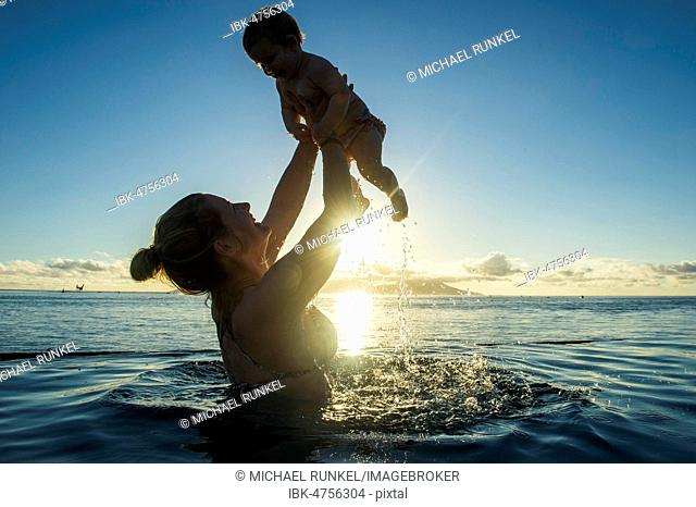 Mother playing with her little baby in the water at sunset, Papeete, Tahiti