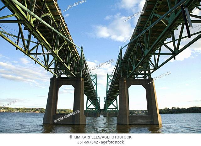 Two interstate highway bridges over waters of Mississippi River, view from underneath from bank of river  Bettendorf, Iowa, USA