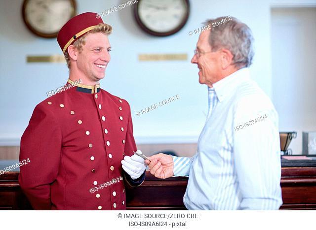 Older man tipping bellhop in lobby