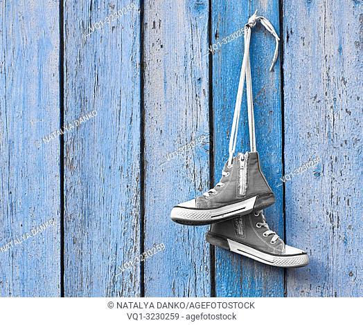 pair of used gray textile shoes hang on a blue background, copy space