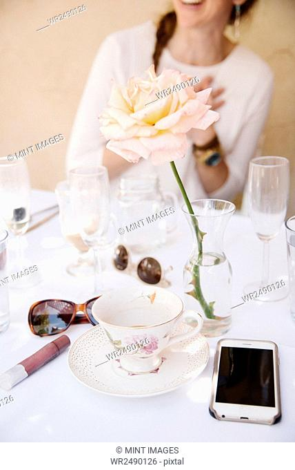 Close up of a rose in a vase on a table with cups and glasses, a cell phone and sunglasses