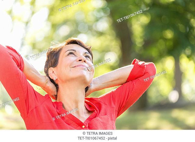 Happy mature woman raising hands in park