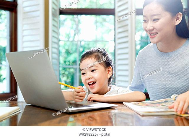 Mother watching laptop with daughter