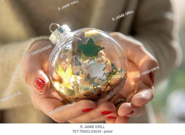 Hands of woman holding Christmas bauble with star shape confetti