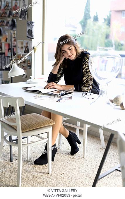 Young designer watching book in her atelier