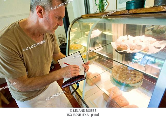Cafe owner checking inventory of confectionery