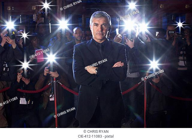 Portrait of serious bodyguard with paparazzi using flash photography in background