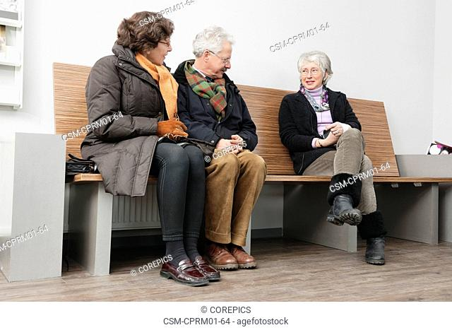 A couple and an older woman chatting in the waiting room of a hospital