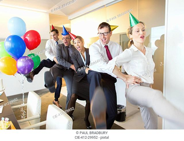 Playful business people with party hats dancing in conga line