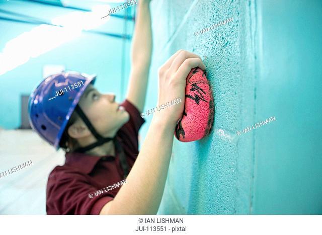 Focused high school student climbing rock climbing wall