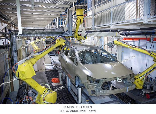 Robots applying sealant to cars in car factory
