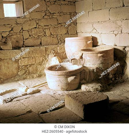 A Minoan wine press at Vathypetro in Crete. The grapes were pressed in the vessel on the right, and fed the juice into the left