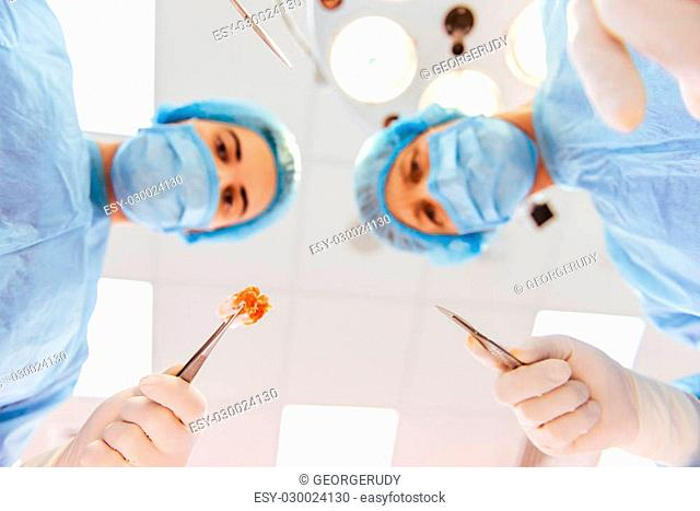 Team surgeons are performing an operation using medical instruments, in a modern operating room, bottom view