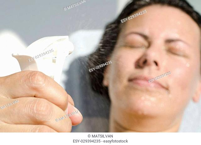 Woman refreshing with water spary when she is sunbathing