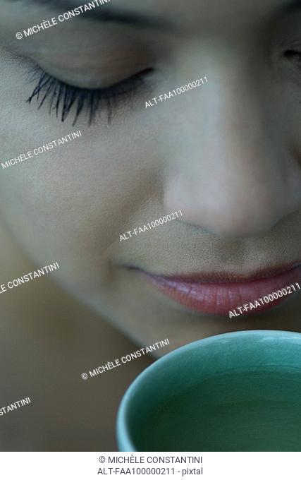 Woman smelling cup of tea with eyes closed, close-up