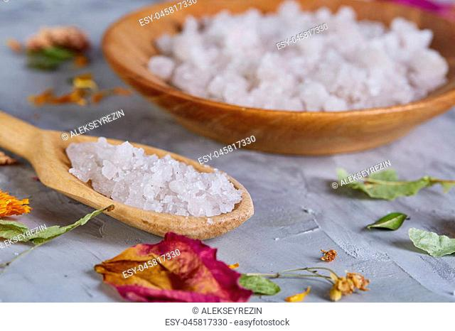 Beautiful composition of spa treatment on white background. Concept spa background with salt in wooden bowl and spoon, close up, top view, selective focus