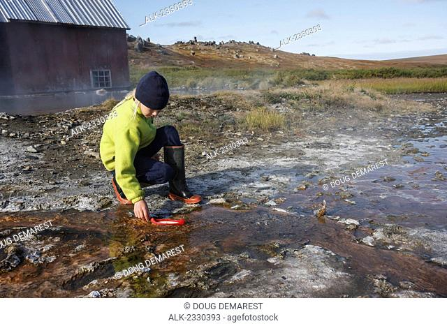 Girl plays with a toy canoe in the creek at Serpentine Hot Springs, Bering Land Bridge National Preserve (National Park), Northwest Alaska, autumn