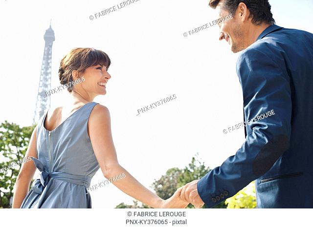 Couple smiling at each other with the Eiffel Tower in the background, Paris, Ile-de-France, France